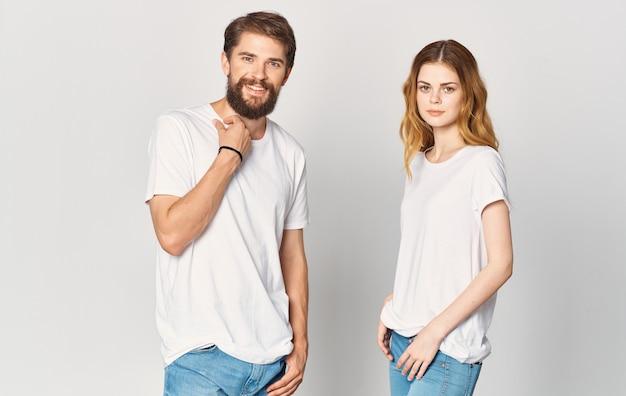 Um homem e uma mulher de jeans e camiseta gesticulam com as mãos emoções divertidas copy space