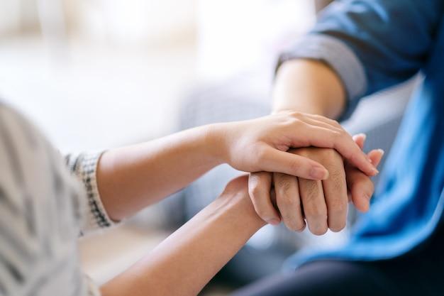 Um homem e uma mulher de mãos dadas para consolo e simpatia