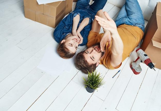 Um homem e uma mulher deitam no chão uma caixa com coisas que renovam a inauguração da casa, vista de cima
