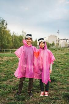 Um homem e uma mulher em pé no campo com uma capa de chuva de plástico rosa compartilhada e fones de ouvido de realidade virtual tirados