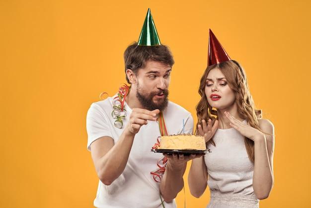 Um homem e uma mulher em um aniversário com um bolinho e uma vela em um boné festivo se divertir e comemorar o feriado juntos, casal feliz