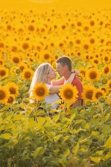 Um homem e uma mulher em um campo de girassóis se beijam e caminham