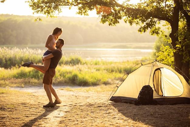 Um homem e uma mulher em uma caminhada com mochilas perto de uma tenda ao pôr do sol estão se abraçando.