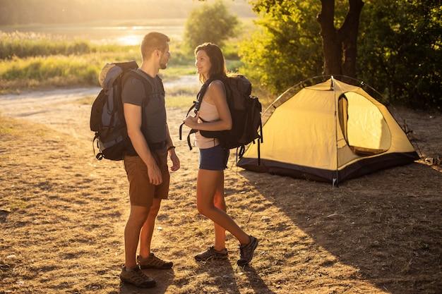 Um homem e uma mulher em uma caminhada com mochilas perto de uma tenda ao pôr do sol. lua de mel na natureza