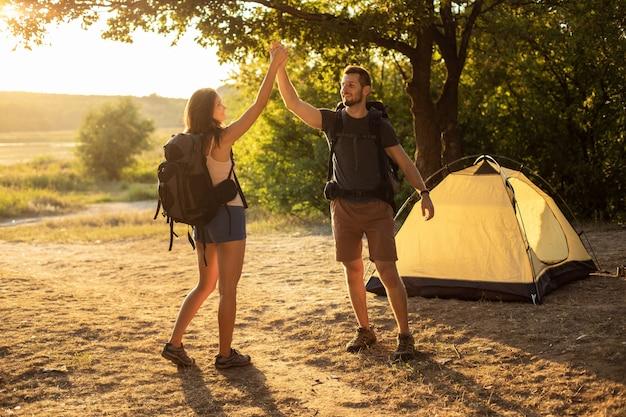 Um homem e uma mulher em uma caminhada com mochilas perto de uma tenda ao pôr do sol, olá cinco. lua de mel na natureza