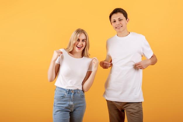 Um homem e uma mulher em uma camiseta branca são mostrados com os dedos nas camisas em um fundo laranja