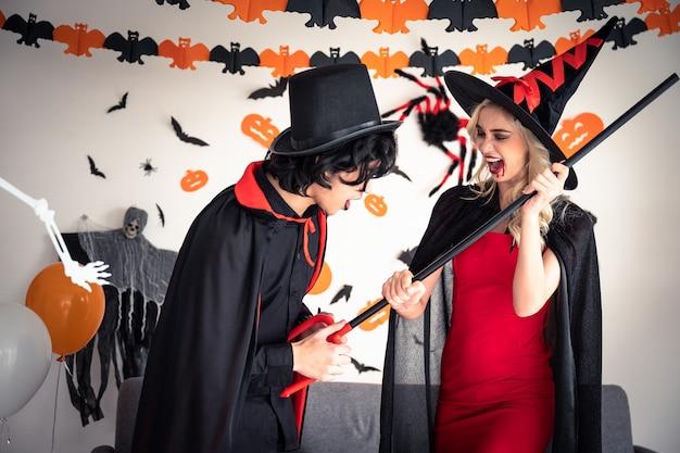 Um homem e uma mulher em vampiros e roupas de bruxa na festa de halloween