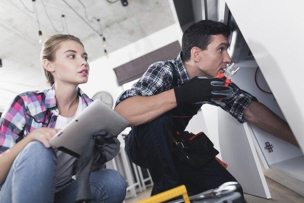 Um homem e uma mulher encanador consertar uma pia
