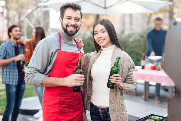 Um homem e uma mulher estão bebendo cerveja durante um piquenique.