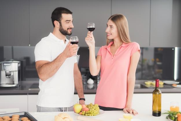 Um homem e uma mulher estão bebendo vinho na cozinha