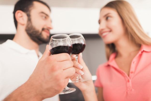 Um homem e uma mulher estão bebendo vinho na cozinha.