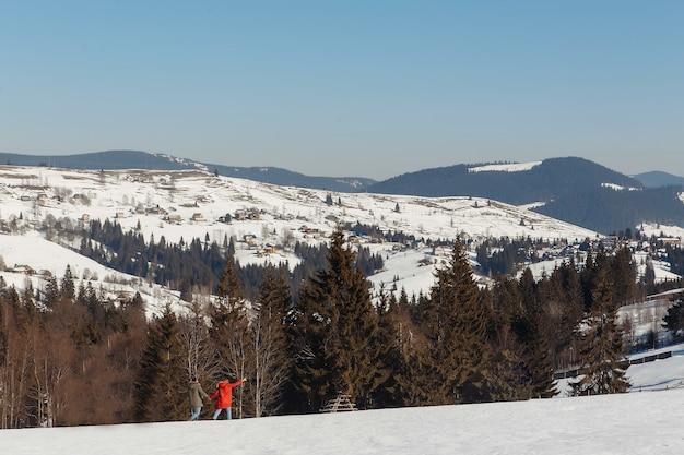 Um homem e uma mulher estão caminhando ao longo das montanhas cobertas de neve os turistas viajam pelas montanhas com uma bela vista altas montanhas na neve belas montanhas nevadas visíveis