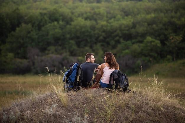 Um homem e uma mulher estão caminhando nas montanhas com mochilas. sente-se relaxando no topo de uma colina.
