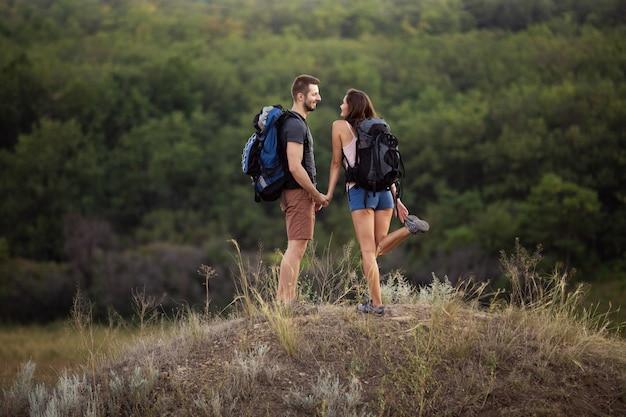 Um homem e uma mulher estão caminhando nas montanhas com mochilas.