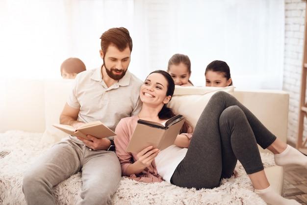 Um homem e uma mulher estão lendo livros no sofá.