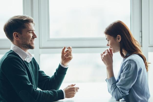 Um homem e uma mulher estão sentados à mesa namorando