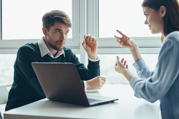 Um homem e uma mulher estão sentados em uma mesa na frente de um laptop falando sobre trabalho