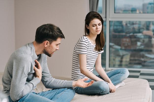Um homem e uma mulher estão sentados na cama e conversando sobre um relacionamento, uma verdadeira briga