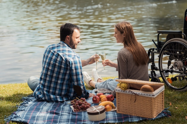 Um homem e uma mulher estão sentados na margem do lago