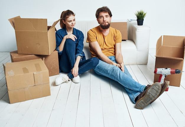 Um homem e uma mulher estão sentados no chão dentro de casa perto do sofá e movendo caixas.