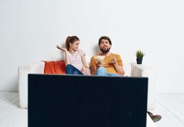Um homem e uma mulher estão sentados no sofá em frente à tv e uma flor verde em um vaso