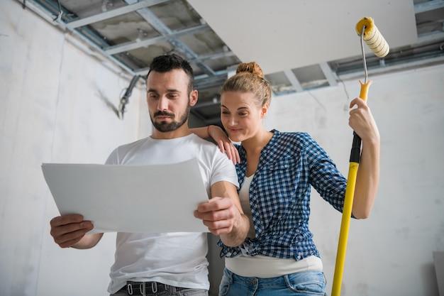 Um homem e uma mulher estão sorrindo e olhando para o plano de trabalho durante a reforma de um apartamento
