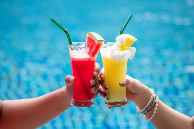 Um homem e uma mulher estavam batendo em um copo de smoothie na piscina do hotel
