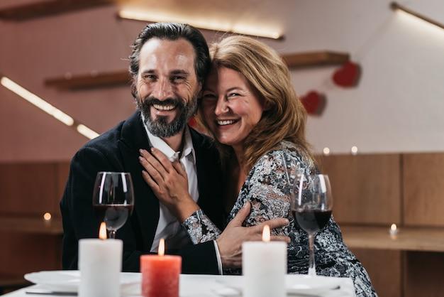 Um homem e uma mulher felizes estão sentando-se e estão abraçando-se em um restaurante.