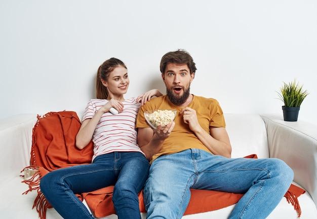 Um homem e uma mulher no sofá assistindo tv