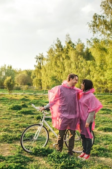 Um homem e uma mulher se olhando romanticamente em capas de chuva de plástico rosa em um encontro com uma bicicleta