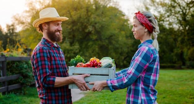 Um homem e uma mulher segurando uma caixa com uma colheita de legumes da fazenda