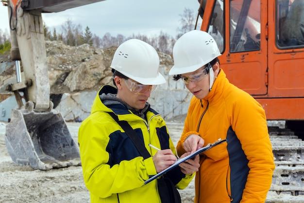 Um homem e uma mulher, trabalhadores de capacetes, assinam um documento no contexto de equipamentos de construção em uma pedreira