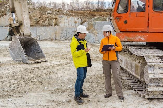 Um homem e uma mulher, trabalhadores ou geólogos com capacetes discutem algo no contexto de equipamentos de construção em uma pedreira