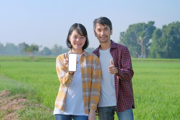 Um homem e uma mulher, um agricultor vestindo uma camisa listrada posa com um smartphone e polegares para cima em um campo.