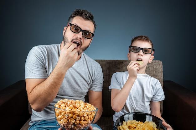 Um homem e uma mulher, uma família assistindo a um filme ou uma série de óculos 3d, uma parede azul. o conceito de cinema, filmes, emoções, surpresa, lazer, plataformas de streaming.