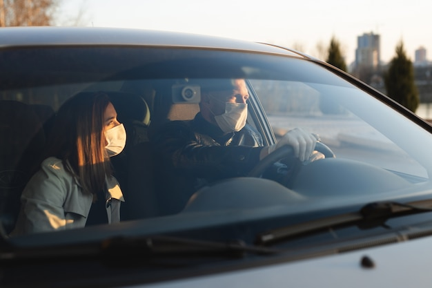 Um homem e uma mulher usando máscaras médicas e luvas de borracha para se protegerem de bactérias e vírus enquanto dirigem um carro. homens mascarados no carro. coronavírus (covid-19