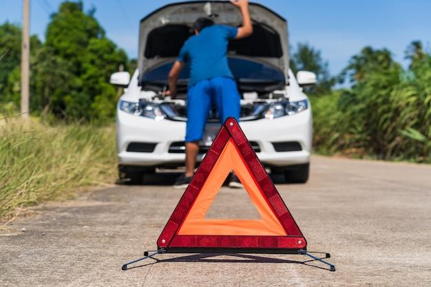 Um homem e vermelho sinal de parada de emergência e um problema branco carro na estrada
