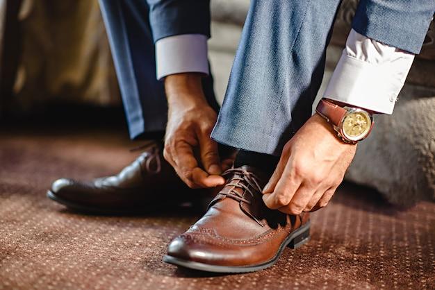 Um homem elegante coloca em preto, couro, sapatos formais.