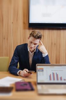 Um homem elegante de casaco e camisa senta-se à mesa com seus colegas e trabalha com documentos no escritório