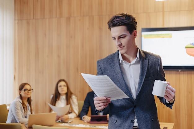 Um homem elegante de jaqueta e camisa com uma xícara de café na mão fica e lê documentos no fundo dos colegas de trabalho no escritório