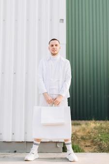 Um homem elegante, vestindo branco depois das compras na black friday