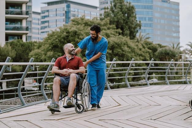 Um homem em cadeira de rodas com seu assistente ao ar livre
