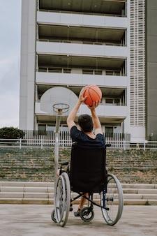 Um homem em cadeira de rodas joga basquete