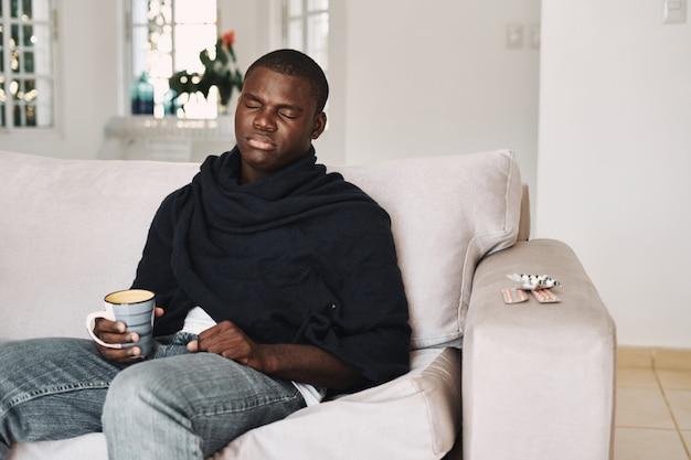 Um homem em casa no sofá com um remédio para resfriado