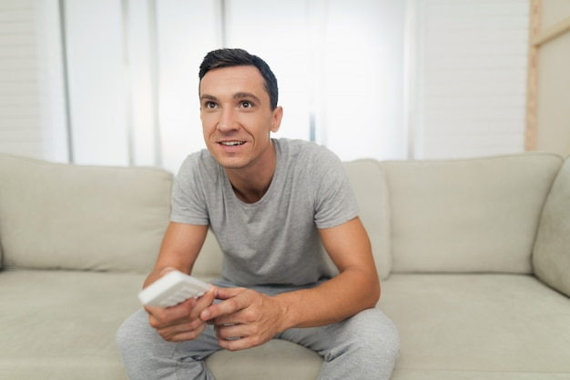Um homem em casa roupa cinza está sentado no sofá e descansando.