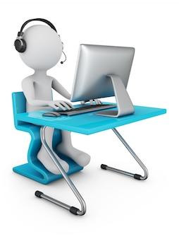 Um homem em fones de ouvido com um microfone se senta em uma mesa com um computador pessoal.