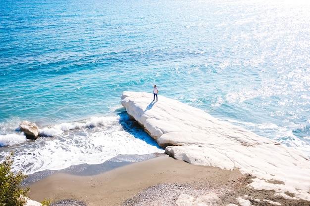 Um homem em pé na costa de um mar