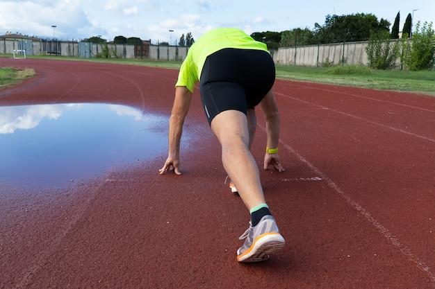 Um homem em posição de começar a correr