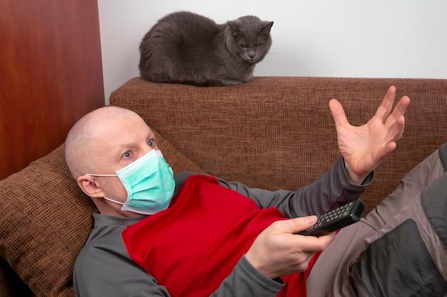 Um homem em quarentena em casa com uma máscara médica no rosto está deitado no sofá e assiste tv ao lado de um gato cinza. descanse durante a epidemia de coronavírus.