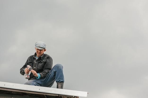 Um homem em roupa de trabalho aperta os parafusos com uma chave de fenda no telhado contra um céu nublado